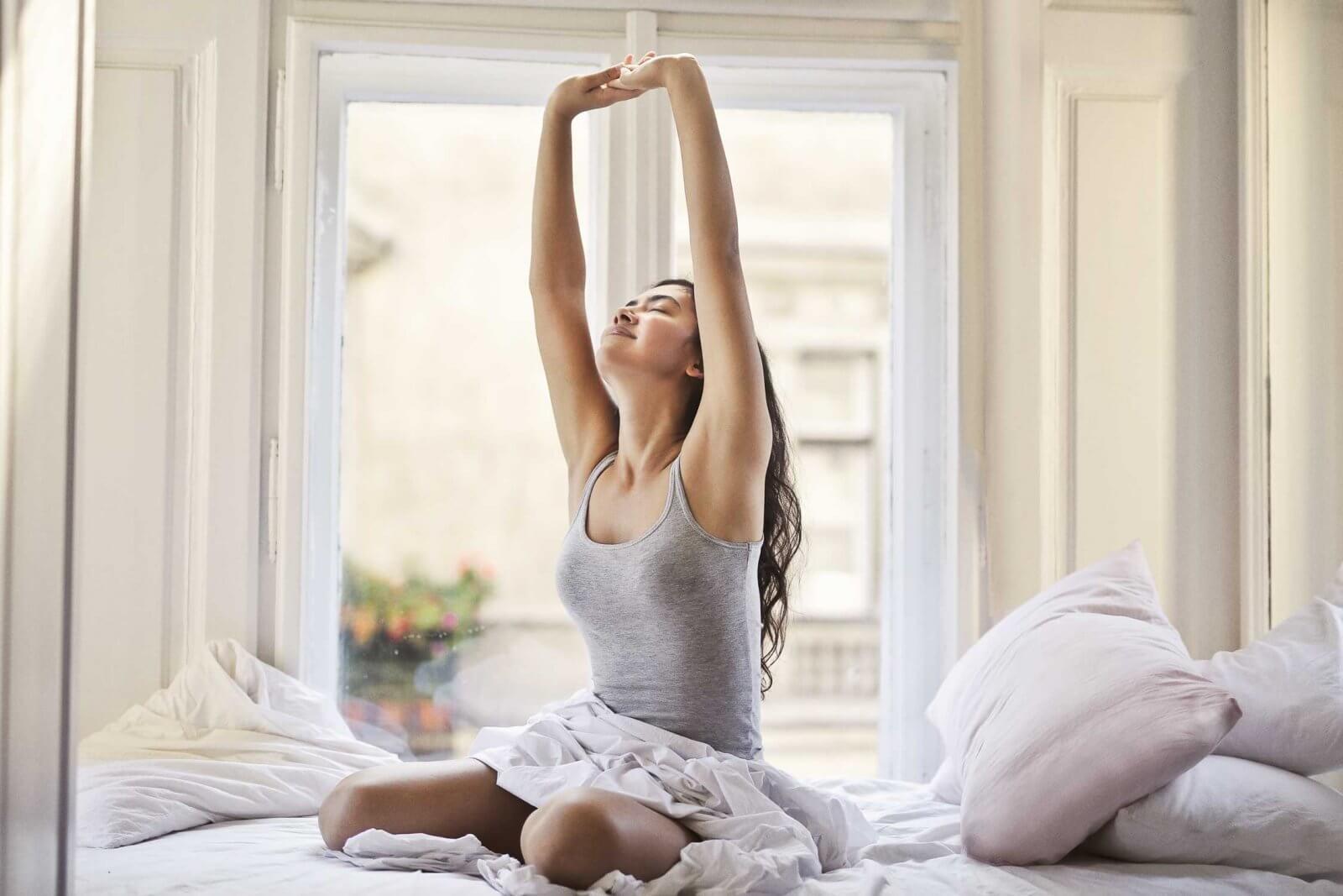 Frau macht Dehnübung im Bett