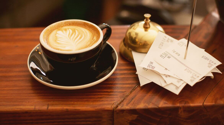 Geld ausgeben für Kaffee: Tasse Kaffee neben Quittungen