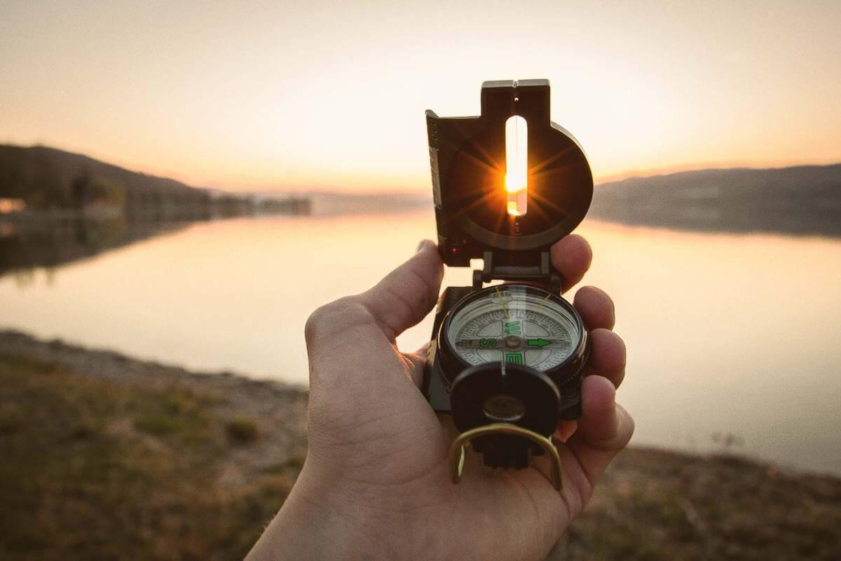 Jemand hält einen Kompass in Richtung Sonne. Das steht symbolisch für Purpose, den Sinn und die Richtung des eigenen Lebens.