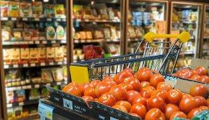 Einkaufswagen im Supermarkt mit Tomaten im Vordergrund
